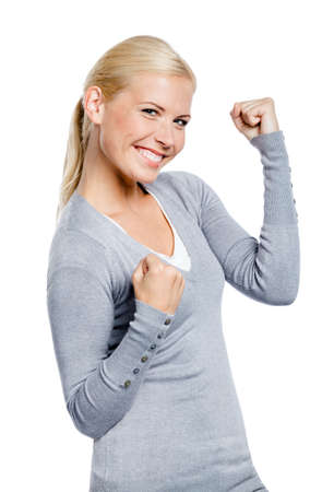 Happy girl in gray sweater with her fists up, isolated on white photo
