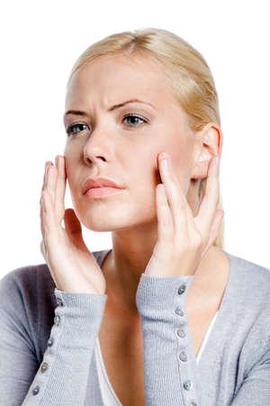 grigiastro: Donna esaminando il suo viso e le rughe che possono comparire, isolato su bianco Archivio Fotografico