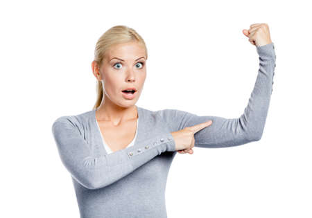 bicep: Woman in grey sweater touching her muscles on hand, isolated on white Stock Photo