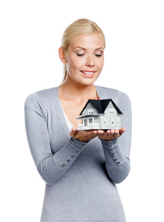 Half-length portrait of female in grey pullover with small model house, isolated on white photo
