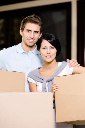 pasteboard: Happy couple carrying pasteboard packages while moving to new house