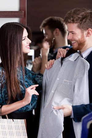gladly: Hombre joven que consulta con su novia mientras se selecciona una camisa elegante