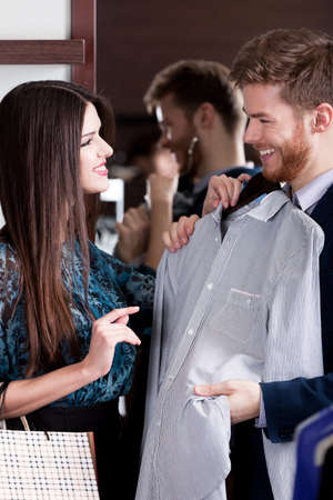Young man consults with girlfriend while selecting a stylish shirt photo
