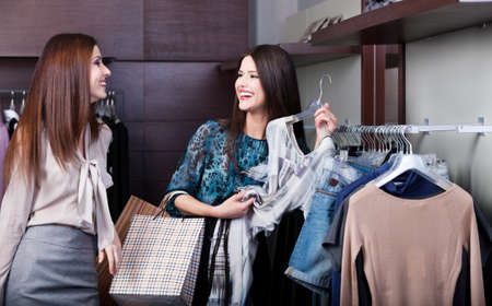 chose: Two girlfriends are joking while do shopping at the store