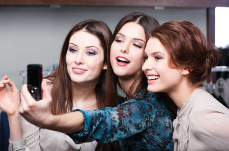 three women: Smiling girls photo session on the mobile phone after shopping Stock Photo