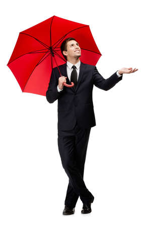 Palming up man with opened umbrella checks the rain, isolated on white photo