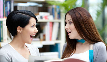 Two glad female students read books at the library photo