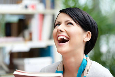 undergraduate: Laughing undergraduate with book at the library. Education and self-development