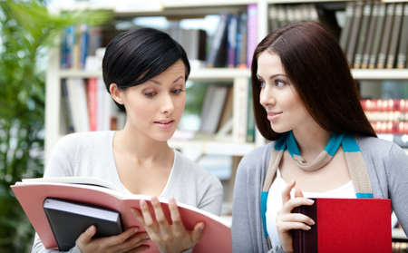 adult intercourse: Two female students read academic books at the library Stock Photo