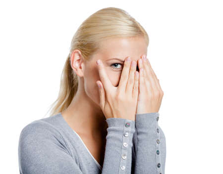 hands covering eyes: Girl covering eyes with hands look through them, isolated on white
