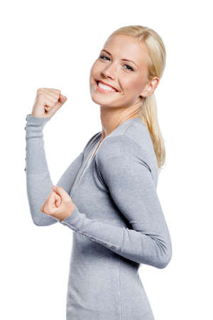 Happy woman in gray sweater with her fists up, isolated on white photo