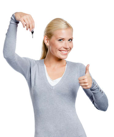 Thumbing up woman in gray sweater keeps a key, isolated on white photo