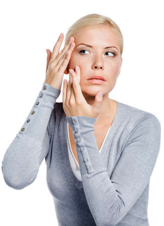 doubtfulness: Lady examining her face and wrinkles that can appear, isolated on white