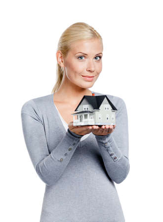 Half-length portrait of woman in grey pullover with small model house, isolated on white photo
