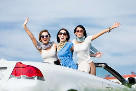 Group of girls stands in the car with hands up. Happy journey of joyful teenagers