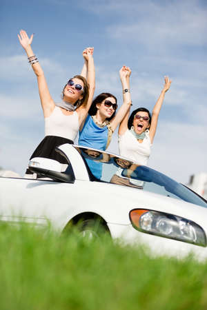 Group of girls stands in the white car with hands up. Happy journey of joyful teenagers photo