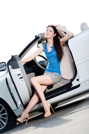 Pretty woman in sunglasses sits in the white car with side door opened photo