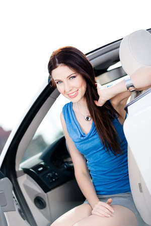 Close up of smiley woman in the car with door opened photo