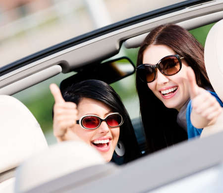 two thumbs up: Two happy girls sitting in the car and thumbing up turn back and have fun while having little car trip