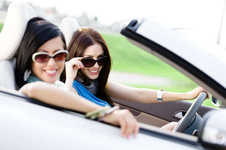 cabriolet: Two happy friends in the car driving everywhere and looking for freedom and fun