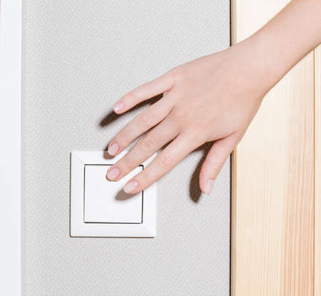 Close up of hand on the white switch panel of electricity