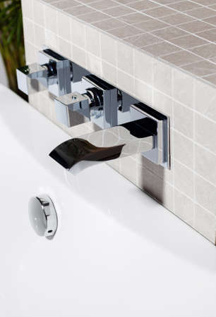 Close up view of mixing faucet in tiled bathroom photo