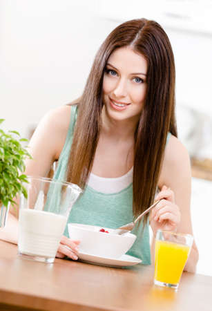 Portrait of the girl eating healthy cereals with milk and orange juice sitting at the kitchen table photo
