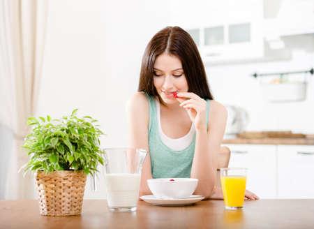 verre de jus d orange: Portrait de la jeune fille mangeant des céréales saines avec du lait et de fraises et jus d'agrumes assis à la table de la cuisine Banque d'images