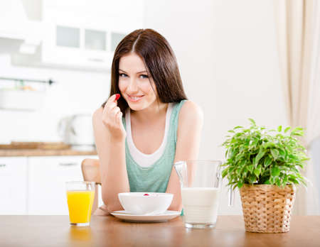 Portrait of the girl eating dieting cereals with milk and strawberry and orange juice sitting at the kitchen table Standard-Bild