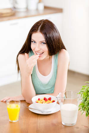 Portrait of the girl eating healthy cereals with milk and strawberry and orange juice sitting at the kitchen table