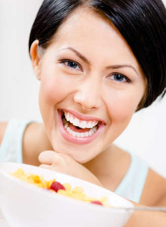 Close up view of girl near the plate with cereals and strawberry photo