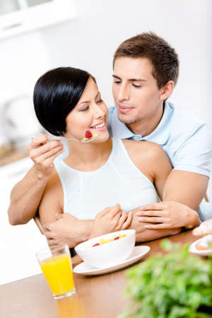 Man feeds and embraces his girlfriend sitting at the kitchen table. Concept of healthy and dieting food photo