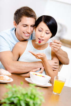 Male feeds and hugs his girlfriend sitting at the kitchen table. Concept of healthy and dieting food photo