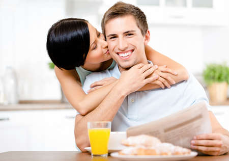 Girl kisses eating boyfriend who sits at the kitchen table with meal and reads the newspaper photo