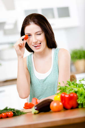 Woman keeps tomato sitting at the table with a great variety of groceries for salad photo