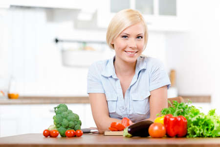 Woman sitting at the kitchen table with vegetables is ready to prepare salad for breakfast Stock Photo - 19411750