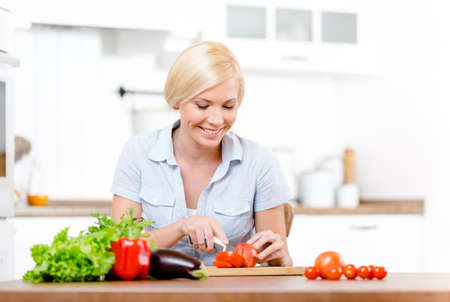Woman cuts groceries for salad sitting at the kitchen table Stock Photo - 19411598