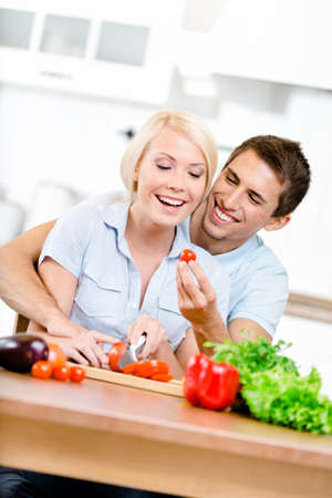 women and men: Couple cooking breakfast sitting together at the breakfast table full of vegetables