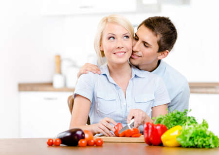 Man kisses girl while she is cooking sitting at the kitchen table full of groceries photo