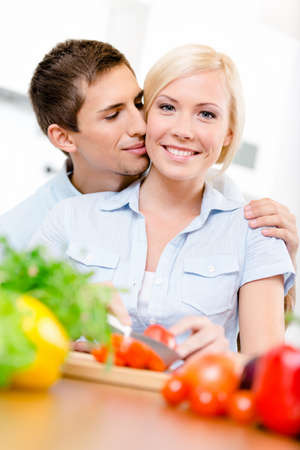 Man kisses young girl while she is cooking sitting at the kitchen table full of vegetables photo