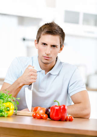 Man with knife is going to prepare breakfast while sitting at the kitchen table full of healthy food Stock Photo - 19411546