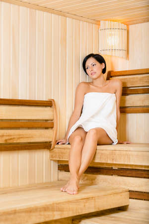 Half-naked lady relaxing in sauna. Concept of self-care, health and relaxation photo