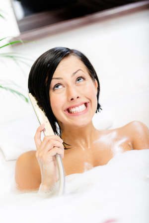 Woman lying in bathtub with suds plays with shower head like phone and relaxes photo