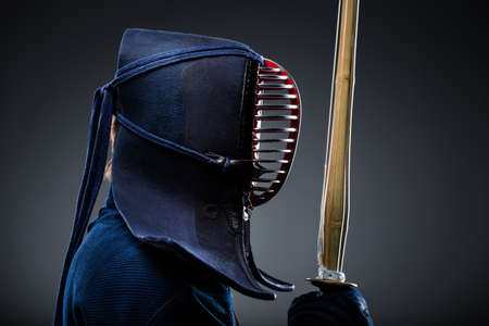 protective workwear: Profile of kendoka with shinai. Japanese martial art of sword fighting