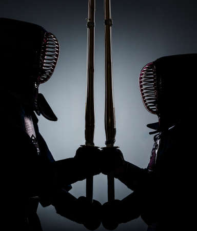 kendo: Two kdark endo fighters opposite each other with bamboo sword. Japanese martial art of sword fighting