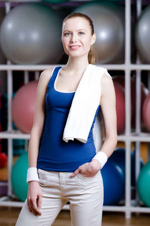 athletic wear: Portrait of a sportive young woman with slim ideal figure in sportswear with white towel Stock Photo