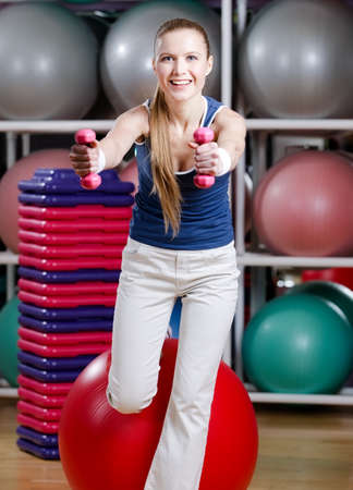 Beautiful sportswoman in sportswear working out with dumbbells photo