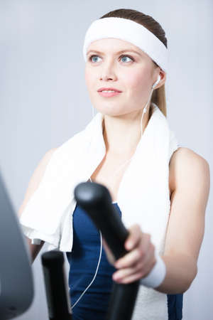 Young athletic woman training on gym equipment in gym photo