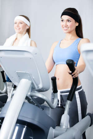 Two young women in sports wear training on simulators in gym photo