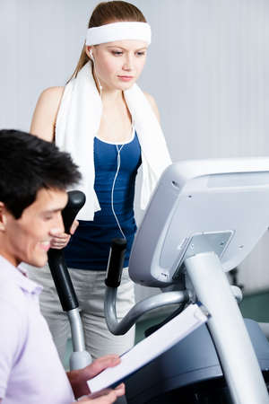 Young athlete woman training on gym equipment in gym with coach writing down the results photo
